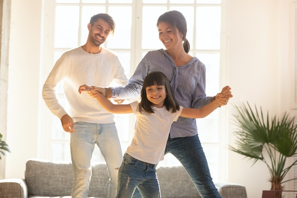 Happy funny family and cute little child daughter laughing dancing in modern living room, joyful parents mom dad with kid girl enjoying moving to music together, mortgage, fun and new home concept