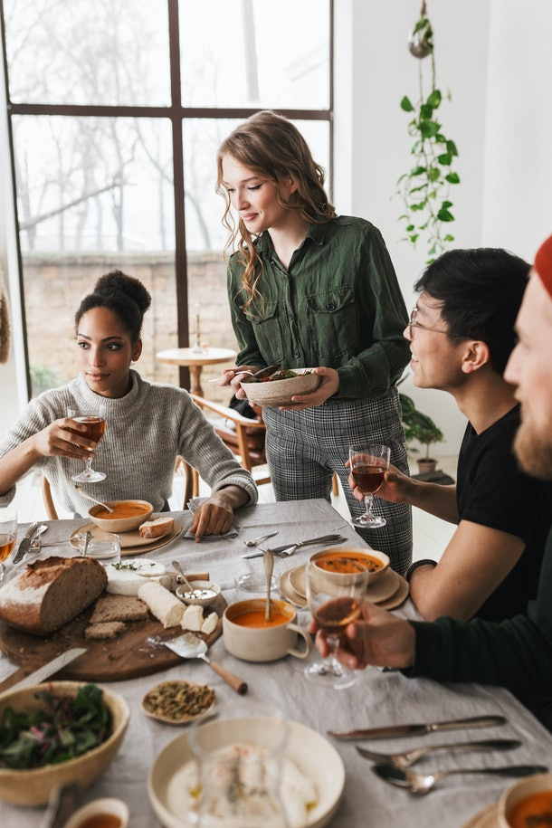 A woman holds a bowl of salad while a group of friends shares a Thanksgiving dinner at a table with a huge spread.