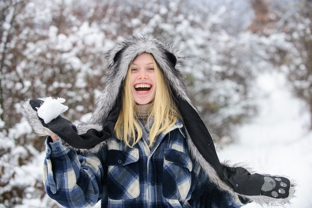 Girl playing with snow. Girl in mittens hold snowball. Happy woman holds snowball in hands. Wintertime. Smiling woman in warm clothing with snowball. Beautiful young woman in winter. Season of winter.