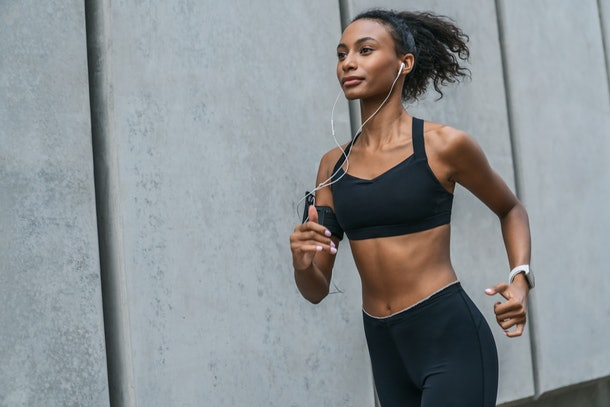 Healthy young woman running in morning outdoors at city streets