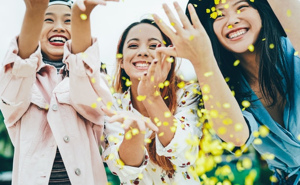 Three happy friends throw yellow flower petals in the air on a spring day.