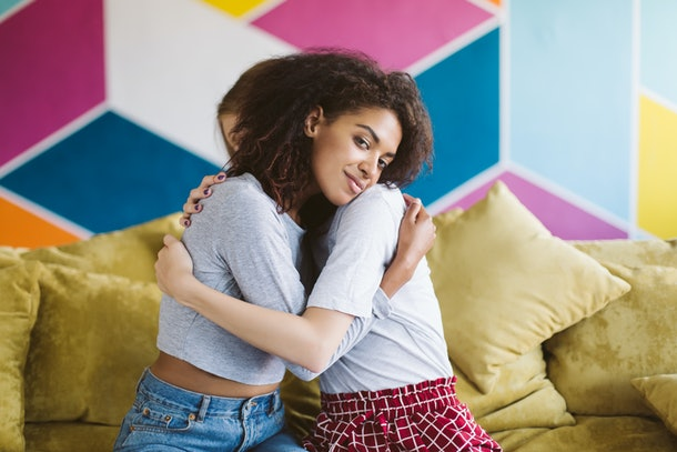 Young pretty african american woman with dark curly hair hugging girlfriend dreamily looking in camera with colorful wall on background
