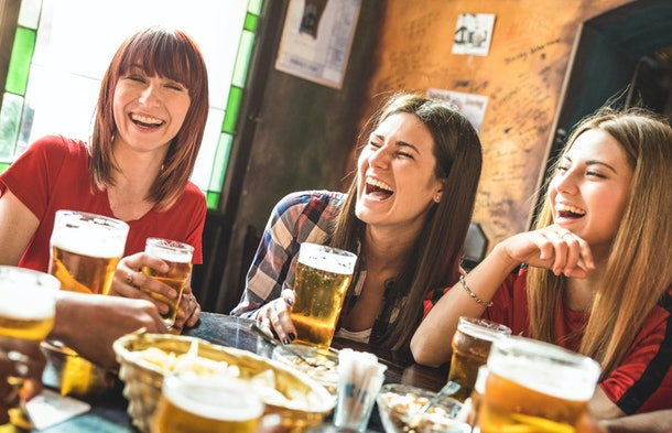A group of friends laugh while drinking beer at a beer hall table.