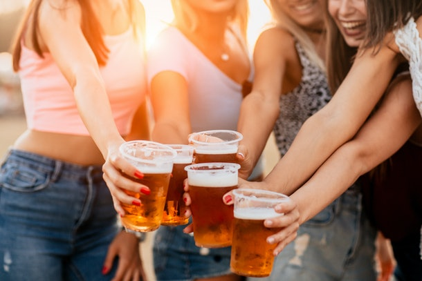 A group of female friends cheers their beer mugs at a brewery.