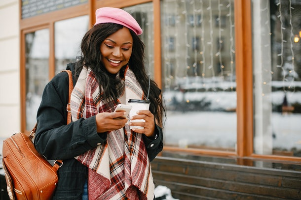 A fashionable woman walks around a city with a backpack, scarf, and pink hat, looking at her phone and holding a holiday drink.