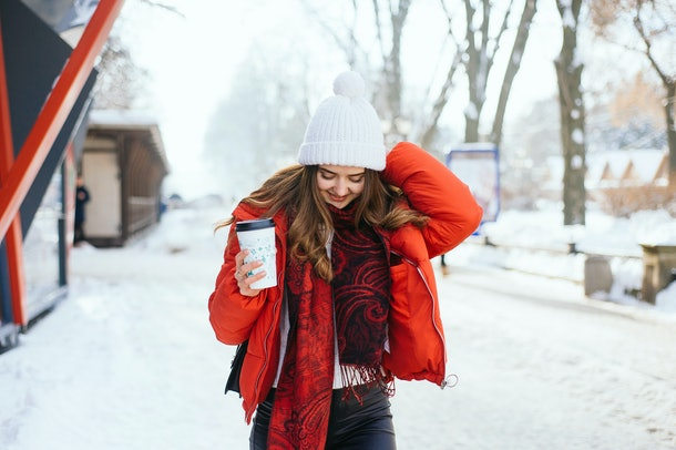 A smiling girl walks through the snow in a red, puffy jacket, with a to-go cup in her hand.