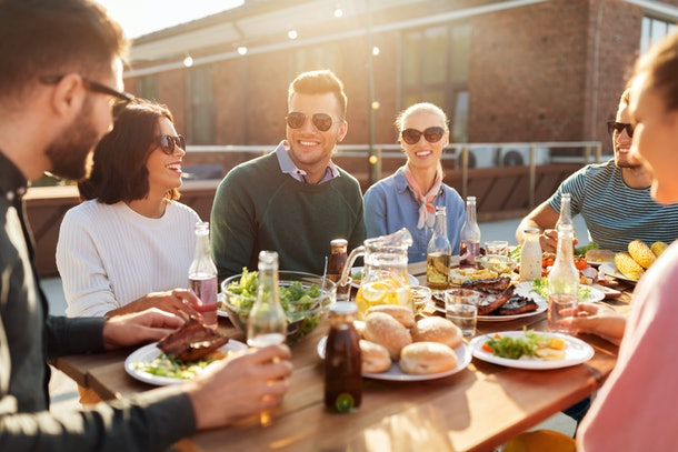 leisure and people concept - happy friends having dinner or bbq party on rooftop in summer