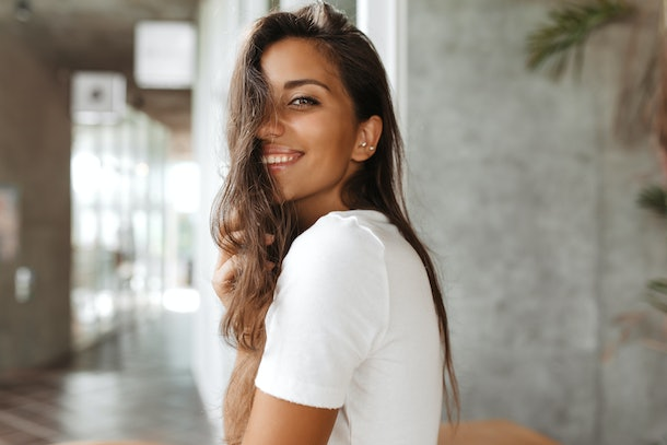 Tanned lady with natural make-up is smiling affably. Brunette girl in light t-shirt poses in gray corridor