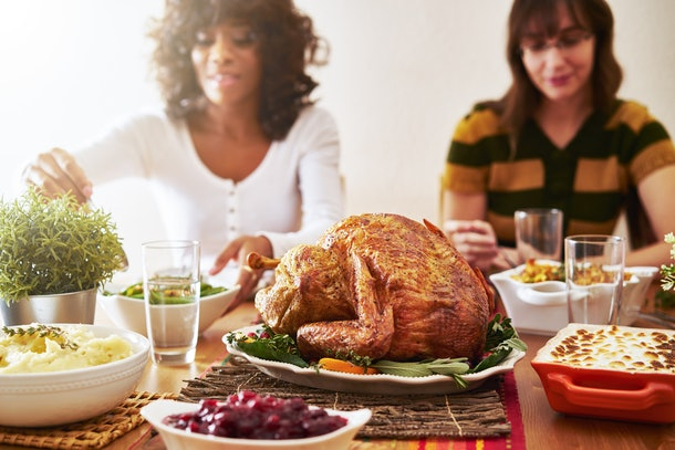 A Thanksgiving dinner spread with turkey, mashed potatoes, cranberry sauce, and people eating in the background.