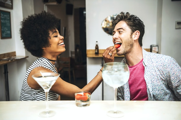 Side view of beautiful woman feeding man with strawberry in bar.