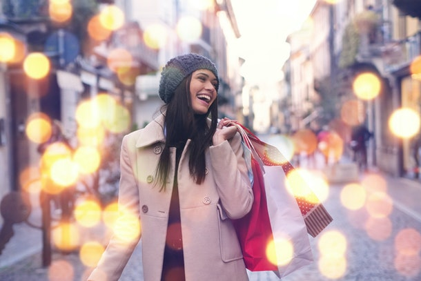 Una niña bonita está sonriendo y feliz comprando en tiendas de la ciudad con rebajas navideñas.  Fantasía: Compras, Vacaciones, Felicidad, Navidad
