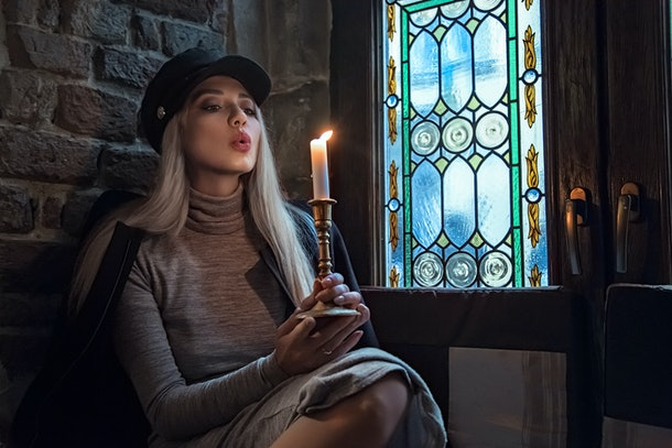 Beautiful girl blowing on a candle in a castle sitting near a stained glass window