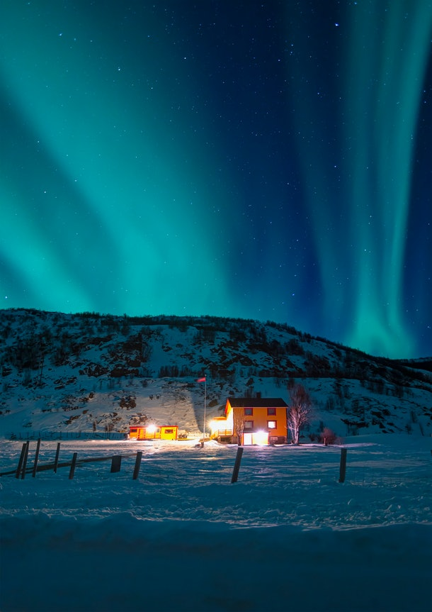 The Northern Lights show up in the night sky over a cozy and welcoming house in the snow.