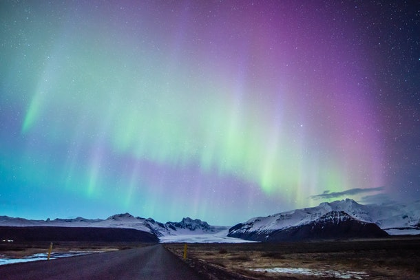 The Northern Lights light up the sky in shades of purple, blue, and green, over a road that runs through the snowy mountains.