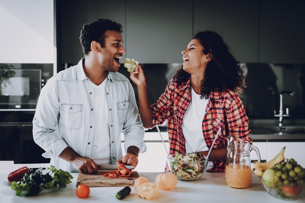 A happy couple cooking makes salad at a white kitchen counter, while the girl laughs and feeds her boyfriend food.