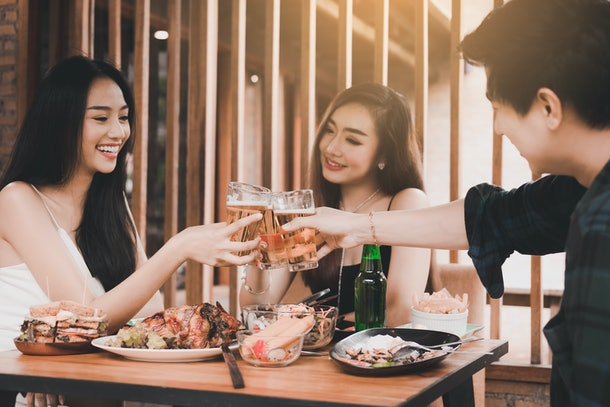 Teenager having enjoy drinking beer and clinking glass in dinner restaurant.