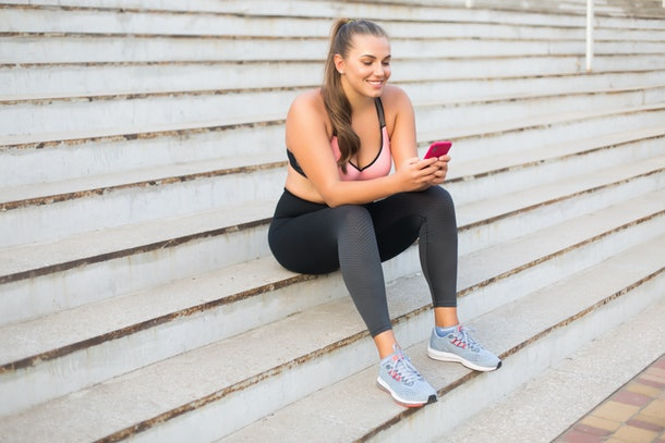 Young cheerful plus size woman in sporty top and leggings sitting on stairs happily using cellphone spending time outdoor