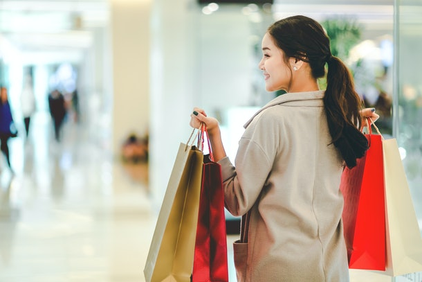 Lifestyle shopping concept, Young happy asian woman with paper bag and coat in shopping mall, vintage style