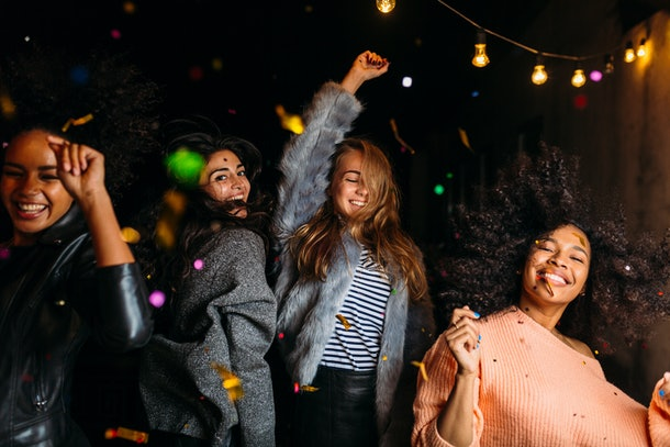 Group of female friends dancing at night under confetti
