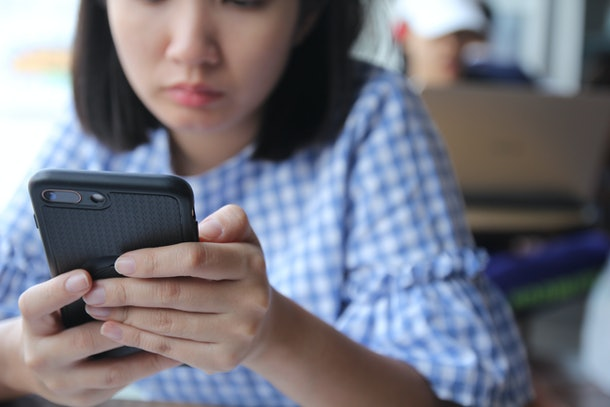 Young stressed woman holding mobile phone feeling angry. Asian girl using cell phone text messaging wirh upset emotion. people technology lifestyle with smart phone concept. Focus on phone.