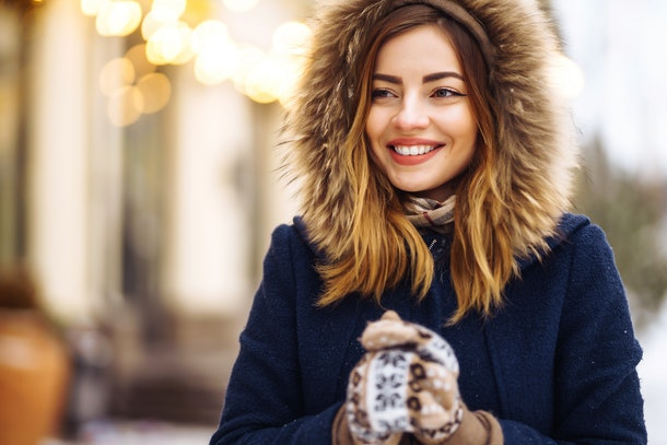 Beautiful  girl in a blue jacket and knitted hat and mittens posing in street of city. Garland lights. Enjoying snow, smiling to camera, cheerful  new year mood, true emotions. Winter fashion.