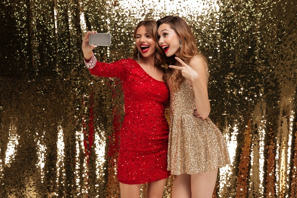 Portrait of two pretty happy women in sparkly dresses taking a selfie while standing together and showing peace gesture isolated over golden shiny background