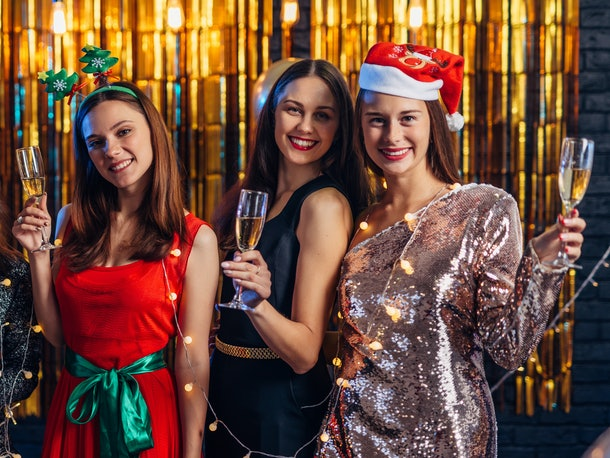 A group of girls smile and pose in front of a shiny gold backdrop dressed in festive attire for SantaCon.