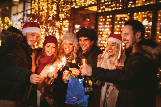 A group of friends laugh with sparklers and champagne at a Christmas party outside.