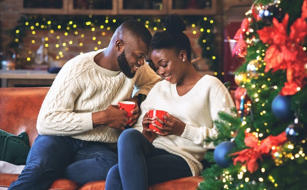 Celebrating Christmas together. Young african couple holding red mugs, reading coffee grounds to learn their fortune, enjoying holidays together.