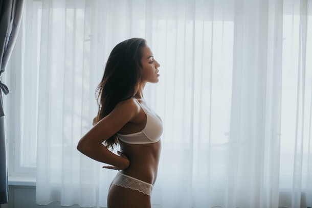 pretty young woman in lingerie by the window