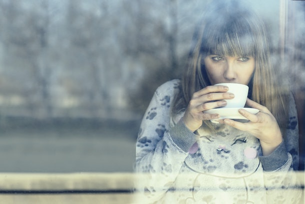 young woman in night dress drinking warm coffee or tea  inside home looking out through the window glass on cold winter morning. concept of lazy winter morning and comfort of a cozy appartment.