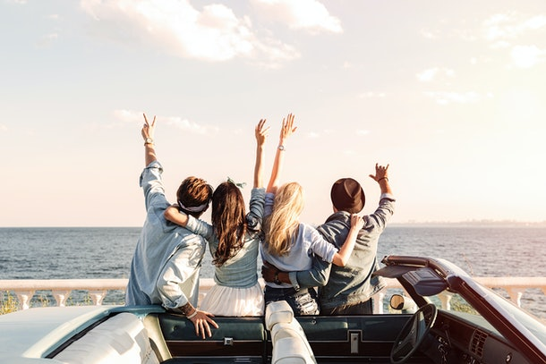 A group of friends stand next to their convertible with their arms up looking at the ocean on a holiday vacation.