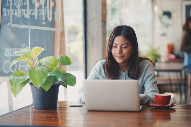 Asian business woman working in coffee shop cafe with laptop