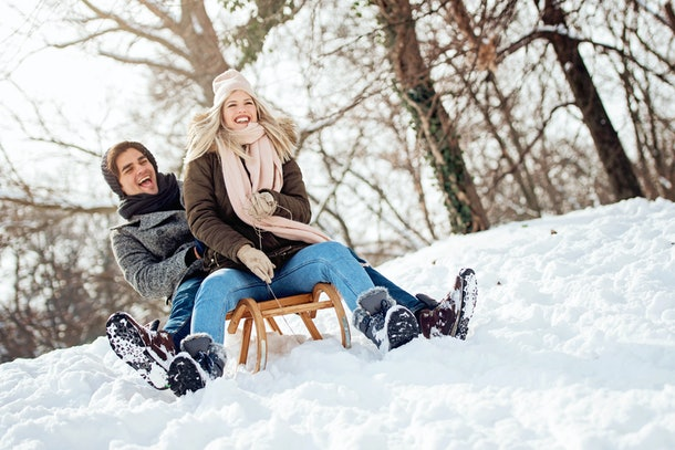 A couple in winter clothing and snow boots laughs as they sled down a snowy hill.