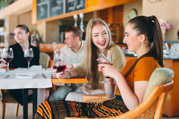 Friends have fun drinking wine, talking and smiling in the restaurant