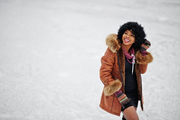 A fashionable woman poses in the snow in a jacket with furry sleeves.