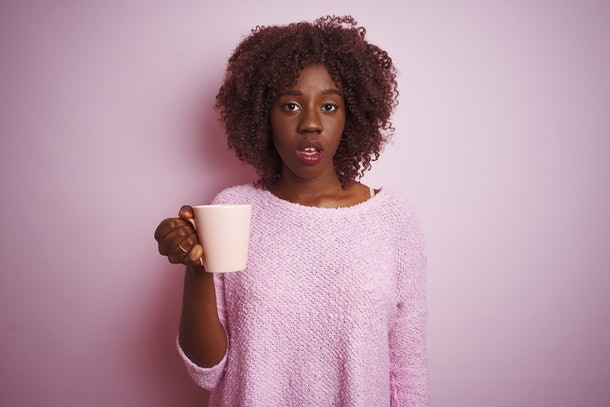 Young african afro woman holding cup of coffee standing over isolated pink background scared in shock with a surprise face, afraid and excited with fear expression