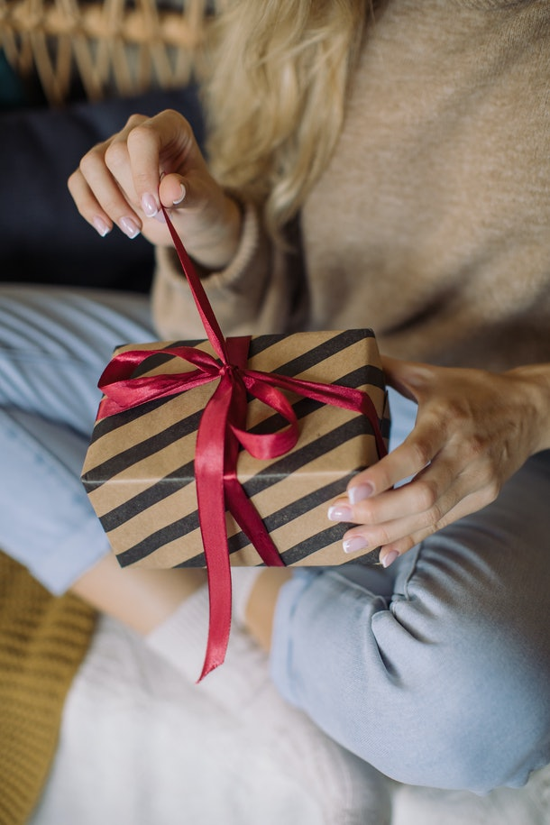 A blonde woman opens up a holiday gift with a red ribbon on Christmas.