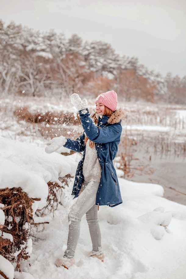 A woman throws snow in the air while hanging out near a lake in the middle of winter.