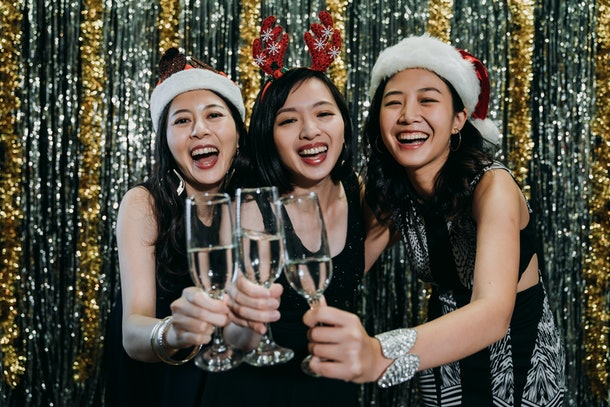 Three friends smile and laugh at a holiday party while they clink their champagne flutes.