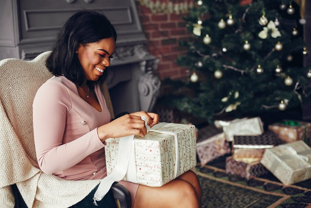 A woman in a fancy pink dress opens a gift while sitting near a Christmas tree.