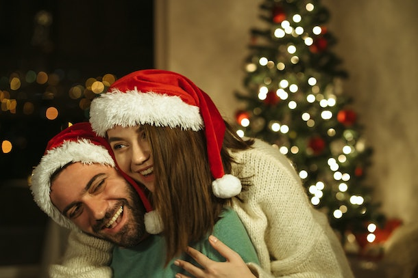 A couple wearing Santa hats hug each other in front of a Christmas tree during the holidays.