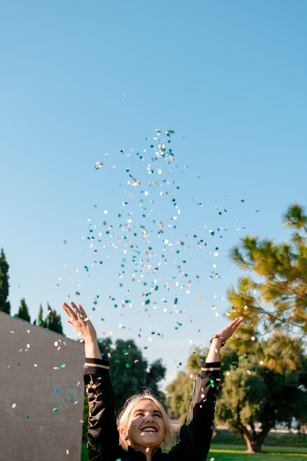 A blonde woman throws confetti in the air on New Year's Eve while hanging out in the sunshine.