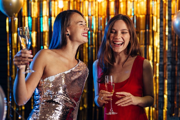 Two girls laugh on New Year's Eve in front of a shiny gold backdrop holding their champagne flutes.