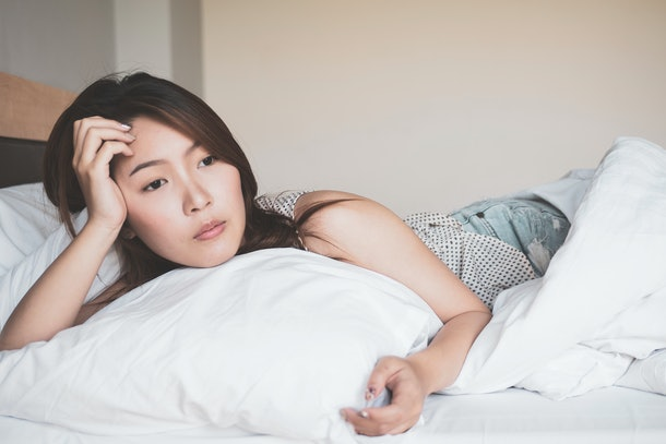 Young asian woman in sad laying on a bed