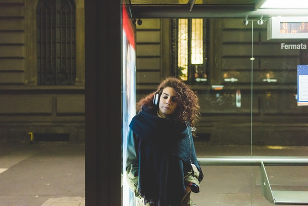 Young beautiful mixed race woman at the bus stop listening music - commuter, technology, music concept