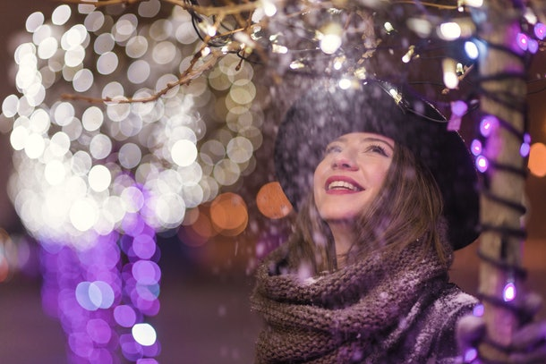 Young girl standing in front of Christmas tree lights at night with snowflakes falling, snowing