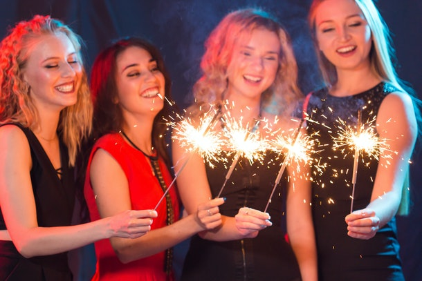 Party, holidays, nightlife and new year concept - happy young women dancing at night club disco