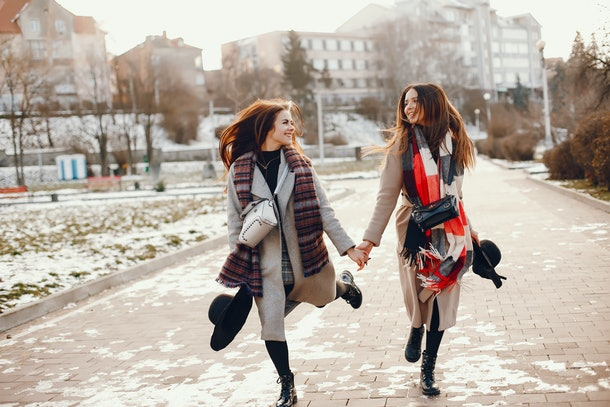 Fashionable girls in a winter city. Stylish ladies in a coats