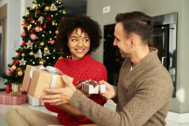 A couple smiles and shares Christmas gifts in their living room over the holidays.